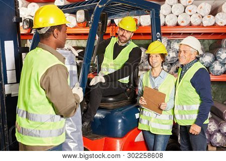 Team warehouse workers with forklift in carpet warehouse prepare a ship