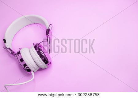 Music Design With Purple Headphones On Pink Colored Background. An