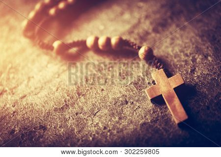 Wooden rosary with cross on stone background. Christian religion. Catholic faith. Prayer.