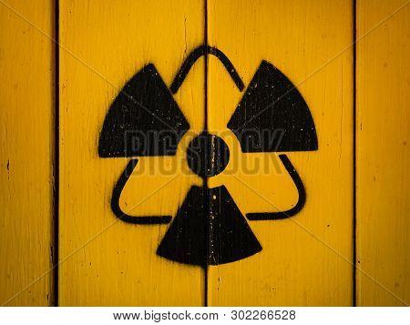 Radioactivity Sign, Close-up. Sign Of Radiation On A Yellow Wooden Board. Radioactive Sign - Symbol
