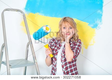 Tired woman ready to makes repairs at home. Sad woman with paint roller, brush and ladder. Girl painting big paint Ukrainian flag on wall at home. Concept of home repair and design.