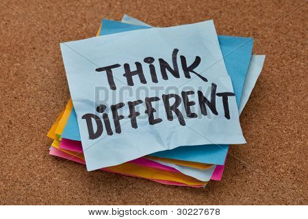 think different concept - motivational phrase on a stack of sticky notes against cork bulletin board