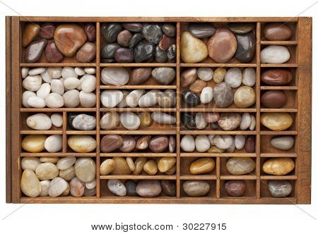colorful river pebbles in vintage wood typesetter drawer isolated with clipping path
