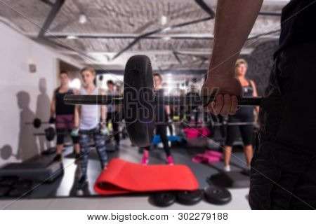 group of young healthy sporty women working out with instructor using barbells while exercises in a fitness studio  fitness, sport, training, gym and lifestyle concept