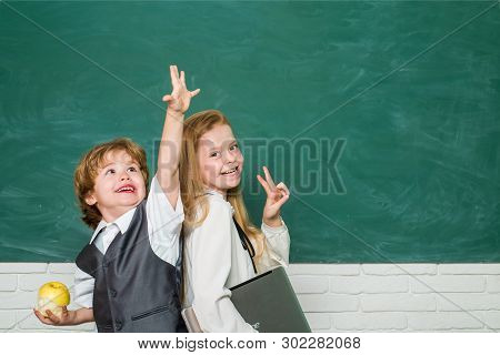 Kids Gets Ready For School. Couple Of Little Girl And Boy In Classroom. Schoolgirl Helping Pupils St