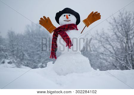 Snow Man. Snowman. Snowman Isolated On Snow Background. Snowman In A Scarf And Hat. Happy Funny Snow