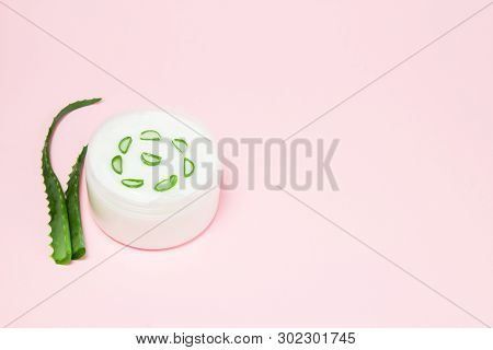 Jar Of Cream And Aloe Vera On A Pink Background. Copy Space