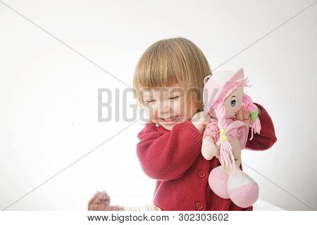 Little Girl Smiling Happy Playing With Doll. Cute Caucasian Baby