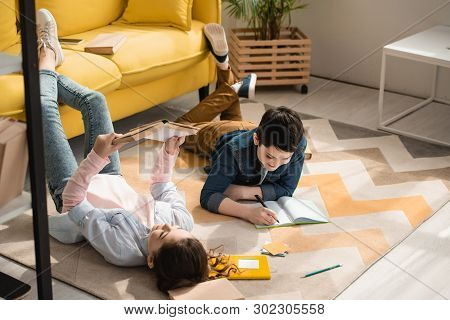 Adorable Kids Lying On Floor At Home And Doing Schoolwork Together