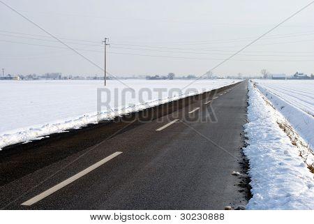 asphalt street in a snow covered farmland landscape