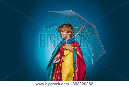 Little Boy With Rainbow-colored Umbrella Isolated On Blue Background. Autumn Mood And The Weather Ar