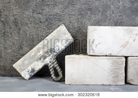 Silicate Bricks, Putty Knife On The Gray Concrete Background. Copy Space. Top View.