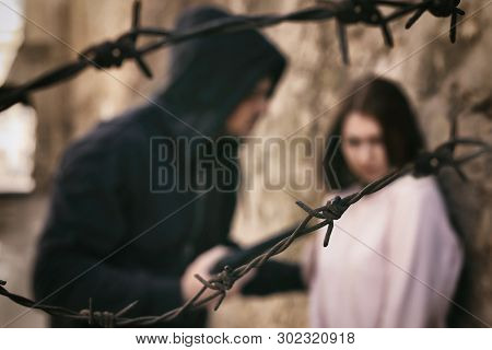 Man Threatening Woman With Gun Outdoors, View Through Barbed Wire. Criminal Offence