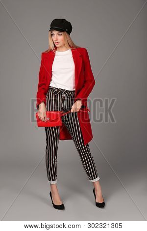 Young stylish woman in trendy shoes with bum bag on grey background poster