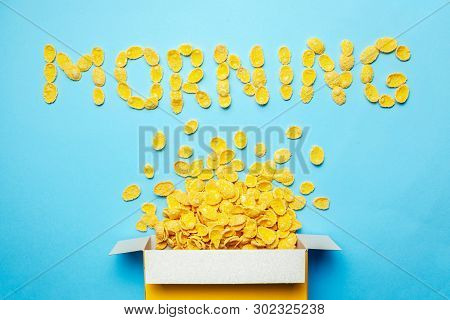 Dry Breakfast Cornflakes. Morning And Placer Flakes From Box On Blue Background.