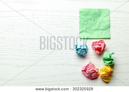 Colored Wrinkled Note Paper On White Wooden Table. Copy Space For Text
