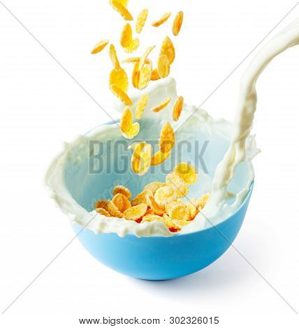 Cornflakes Dry Breakfast With Milk. Stream Of Milk With Cheese And Splash Pours Into Blue Plate With