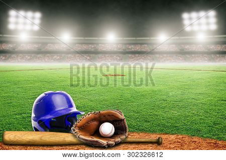Blue Baseball Helmet, Bat, Glove And Ball On Field At Brightly Lit Outdoor Stadium. Focus On Foregro