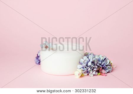 A Jar Of Cream With Flowers On A Pink Background. Copy Space.