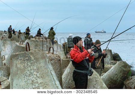 People Fishing From The Sea Pier, Fishermen On The Pier, Baltiysk, Kaliningrad Region, Russia, March