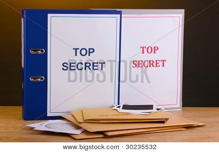 Envelopes and folders with top secret stamp and photo papers with CD disks on wooden table on brown background poster