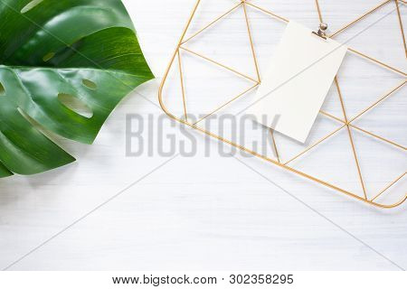 Top View Monstera Leaf And Copper Clip Board Frame With Note Paper On White Wood Table.summer Vacati