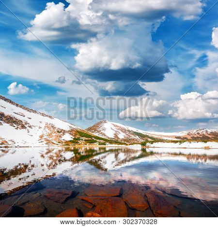 Gorgeous landscape with mountain lake and snowy hills under a blue cloudy sky. Mountains in spring time. Landscape photography