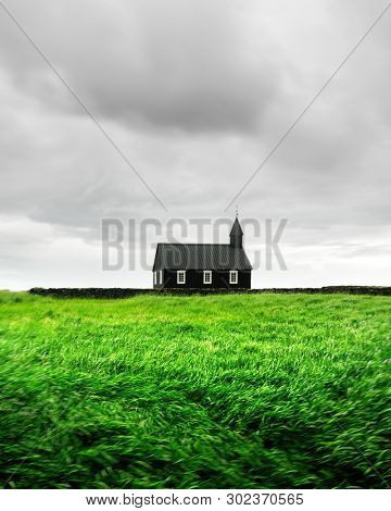Gorgeous landscape with famous picturesque black church of Budir at Snaefellsnes peninsula region in Iceland and field of beauty green grass