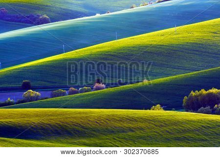 Picturesque rural landscape with green agricultural fields and trees on spring hills. South Moravia region, Czech Republic