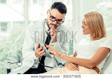 Male Doctor And Female Patient In Hospital.
