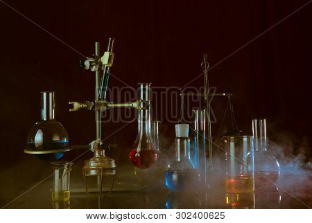 Variety Of Laboratory Vessels With A Colored Reagents In A Rack. Chemical Reaction. Dark Background