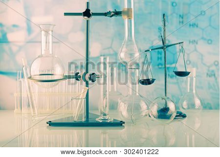 Chemical Cabinet. Tripod With Laboratory Test Tubes And Flasks On The Background Of The Formulas Of