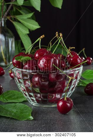 Crystal Bowl With Berries Cherries In Water Drops On Dark Background