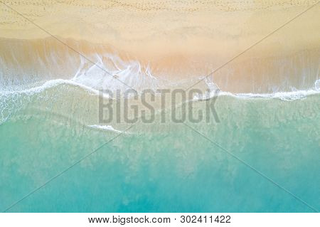 Aerial View Of Turquoise Ocean Wave Reaching The Coastline. Beautiful Tropical Beach From Top View.