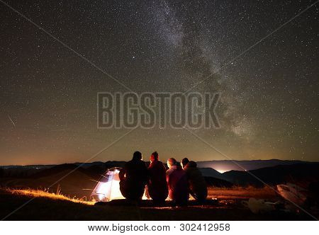 Night Summer Camping In Mountains. Back View Group Of Four Hikers Sitting On A Bench Made Of Logs To