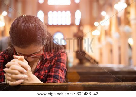 Young Woman Sits On A Bench In The Church And Prays To God. Hands Folded In Prayer Concept For Faith