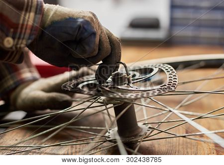 Cropped Shot Of Male Mechanic Working In Bicycle Repair Shop, Worker Fixing Old Bikes Wheel Using Sp