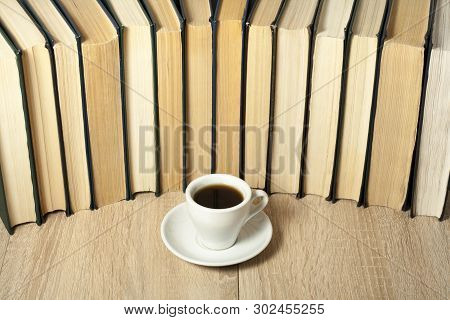 Stack Of Old Books And Cup Of Coffee On Wooden Desk Back To School. Education Background.