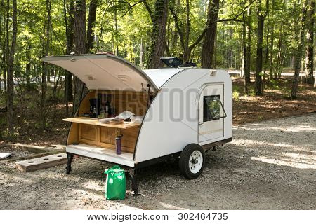 Simple home built teardrop trailer set up at campsite in the forest.