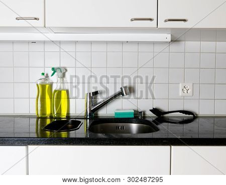 Kitchen Sink And Faucet With A Sponge And Brush On A Black Granite Table Top And Yellow Kitchen Clea