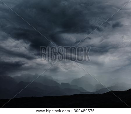 Summer rain in the mountains. Dramatic clouds and mountains silhouette.