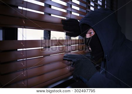 Masked Man With Gun Spying Through Window Blinds Indoors. Criminal Offence