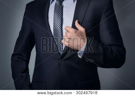 Suit Up. Businessman In A Suit And Tie. Hand On The Lapel Of The Suit.