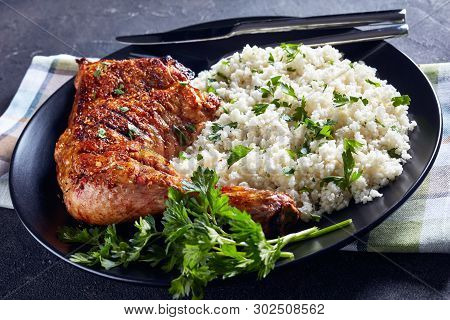 Crispy Broiled Chicken Leg Quarter Served With Cauliflower Rice Or Couscous On A Black Plate On A Co