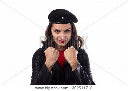 Young woman black jacket, red sweater and hat with a reference to Ernesto Che Guevara looking in camera, demonstrate her fists and smile on a white background with copy space poster