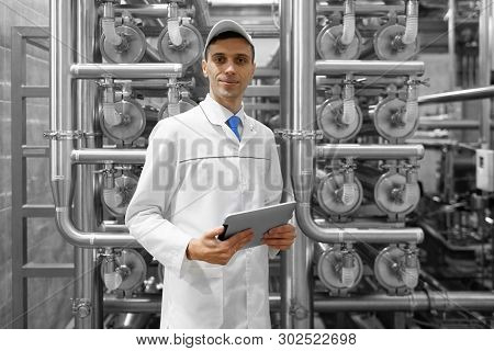 Portrait Of Man In A White Robe And A Cap Standing In Production Department Of Dairy Factory With Gr