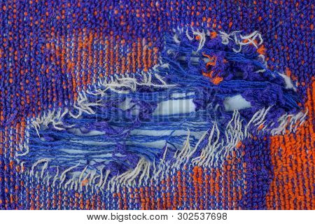 Torn Piece Of Woolen Clothes With A Hole And Blue Threads