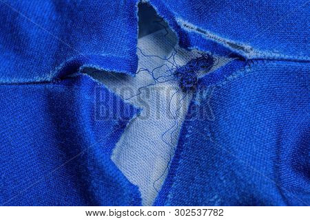 A Piece Of Tattered Clothing With A Big White Hole On Blue Matter