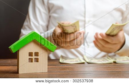 A Man Counts Money On The Background Of The Figures Of The House. Calculation Of Property Tax, Payme
