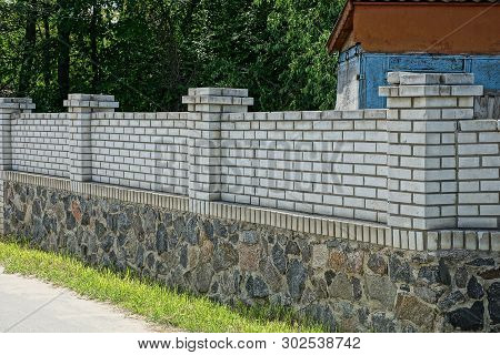 A Long Private Fence Of White Bricks And Gray Stones Outside In Green Grass